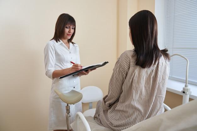 Vrouwelijke arts-gynaecoloog die medische adviezen aanbiedt aan een jonge vrouwenpatiënt in kliniek Premium Foto