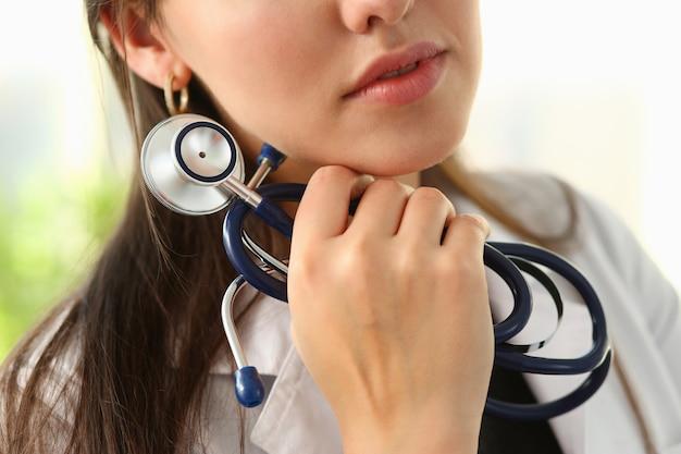 Vrouwelijke arts hand houden phonendoscope in medische kleding Premium Foto