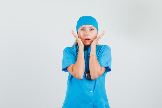 Vrouwelijke arts hand in hand in de buurt van gezicht in blauw uniform en bang op zoek Gratis Foto