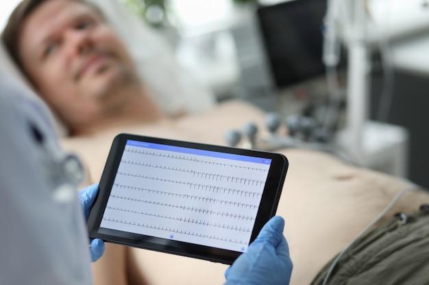 Vrouwelijke arts houdt tablet met elektrocardiogram Premium Foto