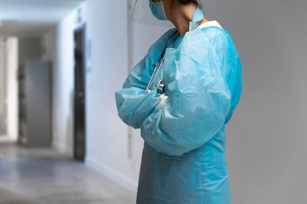Vrouwelijke arts in beschermende kleding wegkijken in de gang Gratis Foto