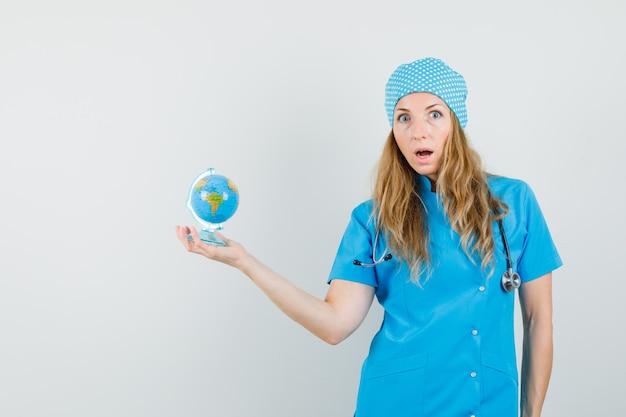 Vrouwelijke arts in blauw uniform wereldbol te houden en angstig te kijken Gratis Foto