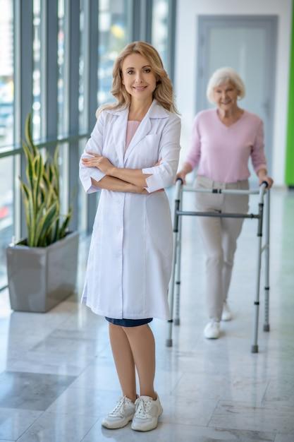 Vrouwelijke arts in een laboratoriumjas die zich met gekruiste wapens bevindt en glimlacht terwijl haar patiënt naar haar komt Premium Foto