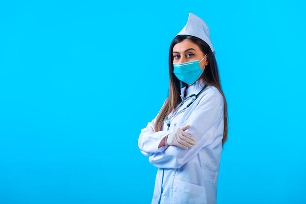 Vrouwelijke arts in masker doet zich voor als een professional. Gratis Foto