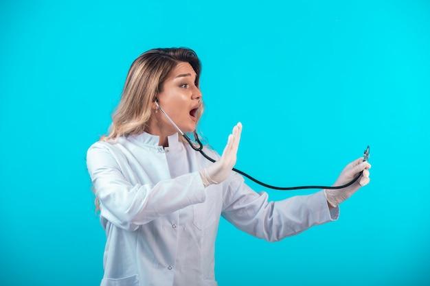 Vrouwelijke arts in wit uniform controleren met een stethoscoop. Gratis Foto