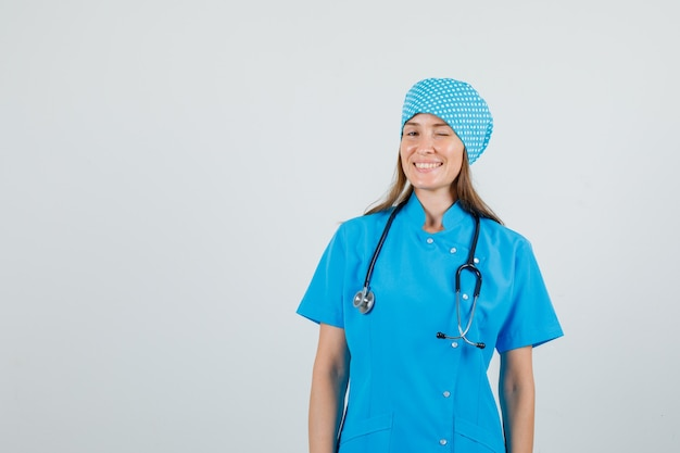 Vrouwelijke arts knipperend oog en lachend in blauw uniform Gratis Foto