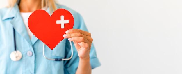 Vrouwelijke arts met het document hart van de stethoscoopholding met exemplaarruimte Premium Foto