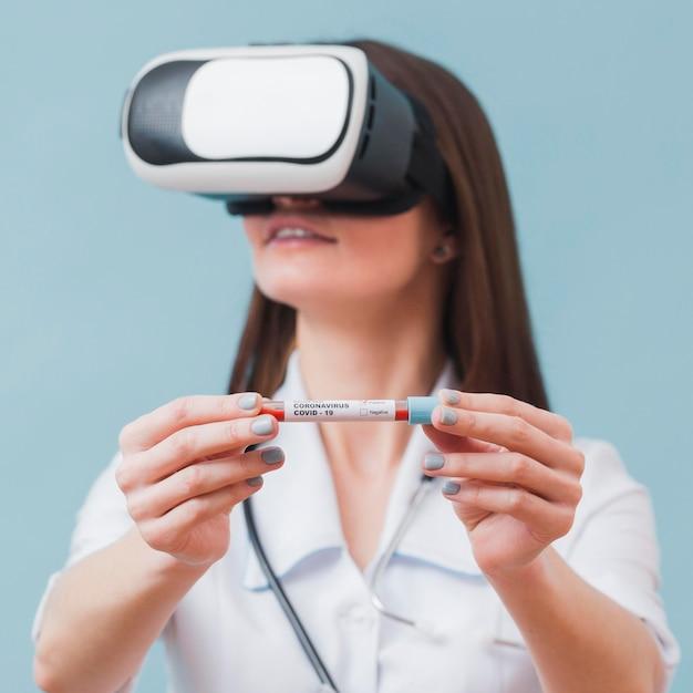 Vrouwelijke arts met virtual reality headset met coronavirus reageerbuis Gratis Foto