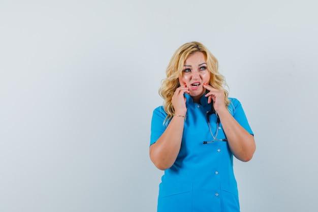 Vrouwelijke arts raakt haar opengevallen kaak in blauw uniform aan en ziet er ingewikkeld uit. ruimte voor tekst Gratis Foto