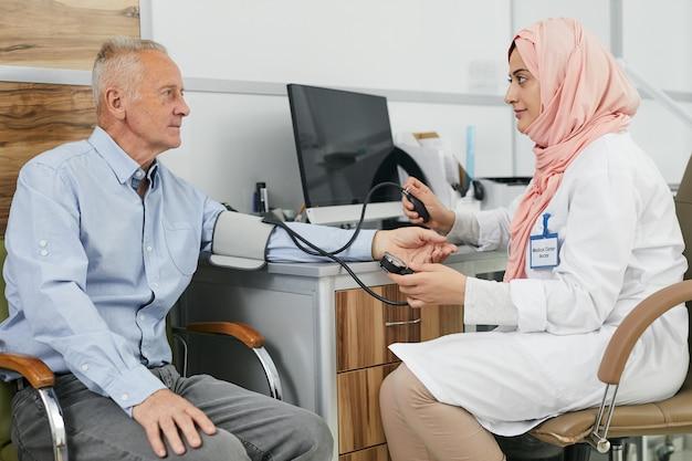 Vrouwelijke arts uit het midden-oosten die met hogere patiënt spreekt Premium Foto