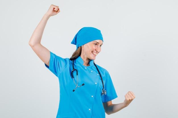 Vrouwelijke arts vieren overwinning met opgeheven vuisten in blauw uniform en op zoek gelukkig Gratis Foto