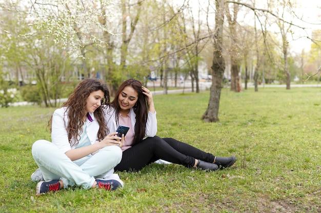 Vrouwelijke artsenstudent in openlucht met telefoon. medische achtergrond Premium Foto
