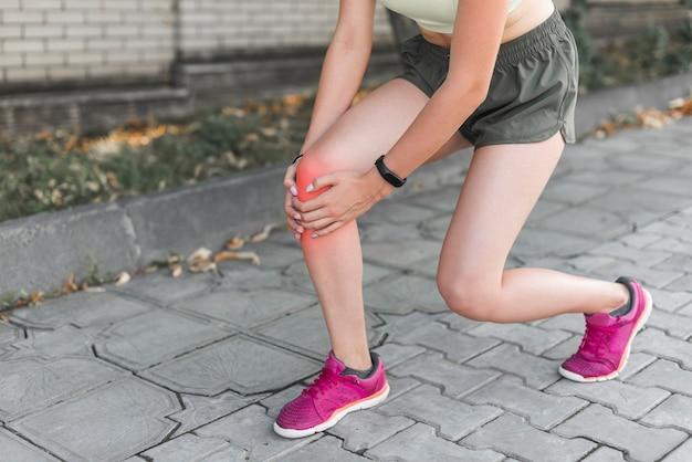 Vrouwelijke atleet die pijn in knie heeft Premium Foto