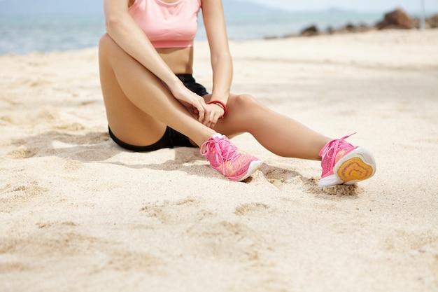 Vrouwelijke atleet met mooie benen dragen roze loopschoenen zittend op zandstrand, met een kleine pauze na actieve training buiten aan de oceaan. Gratis Foto