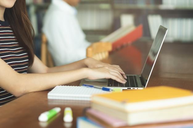 Vrouwelijke aziatische student die en boek in bibliotheek bestudeert leest Premium Foto