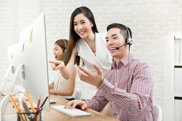 Vrouwelijke aziatische supervisor die het werk bespreekt met haar team in call centre Premium Foto