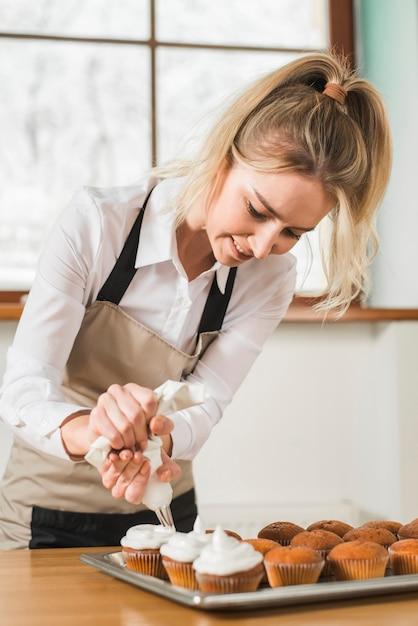 Vrouwelijke bakker die cupcake met witte boterroom verfraait door de suikerglazuurzak in te drukken Gratis Foto