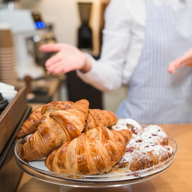 Vrouwelijke bakker die de gebakken croissants in de caketribune voorstelt Gratis Foto