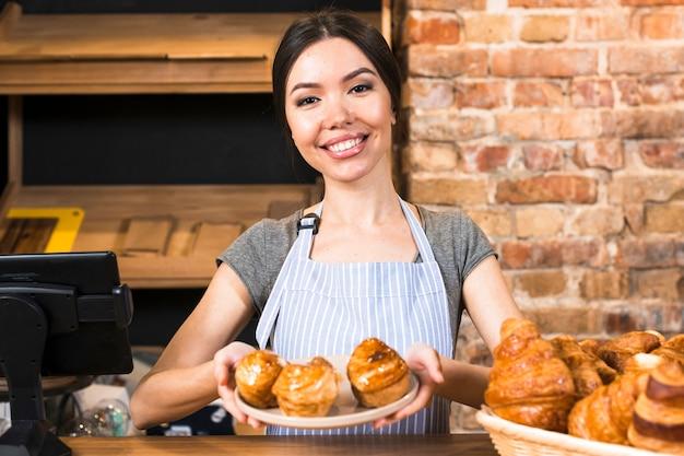 Vrouwelijke bakker die gebakken zoete bladerdeeg op plaat tonen bij de bakkerijwinkelteller Gratis Foto