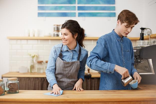 Vrouwelijke barista die onderaan lijst sponst die gelukkig glimlacht. maak koffie schenken. Gratis Foto