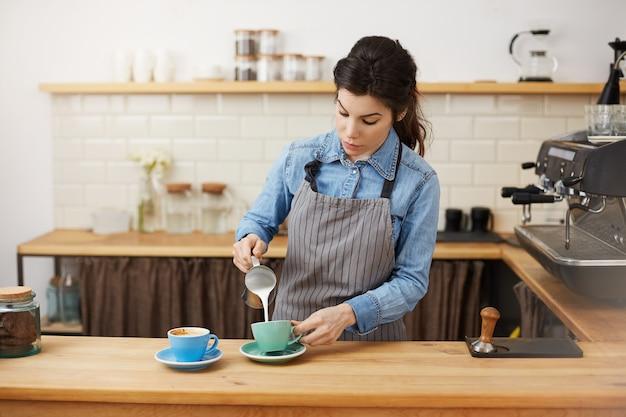 Vrouwelijke barista giet melk, waardoor twee cappuccino, geconcentreerd. Gratis Foto