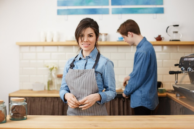 Vrouwelijke barista in uniform glimlachend vrolijk bestellingen opnemen. Gratis Foto