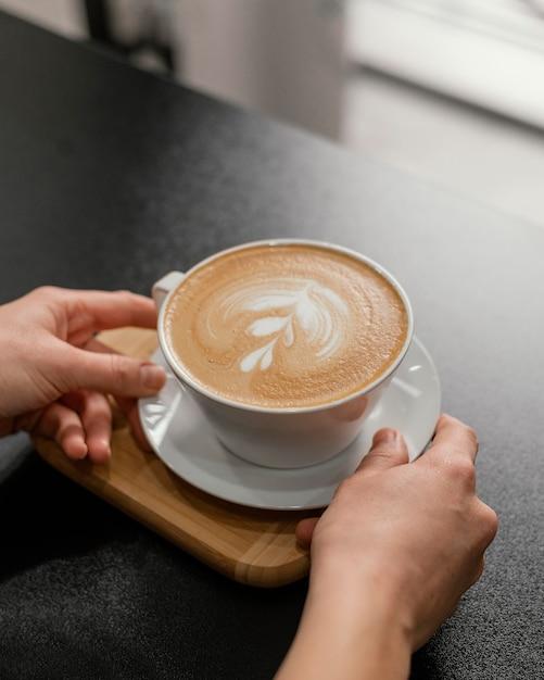 Vrouwelijke barista ingericht kopje koffie op het aanrecht te plaatsen Gratis Foto