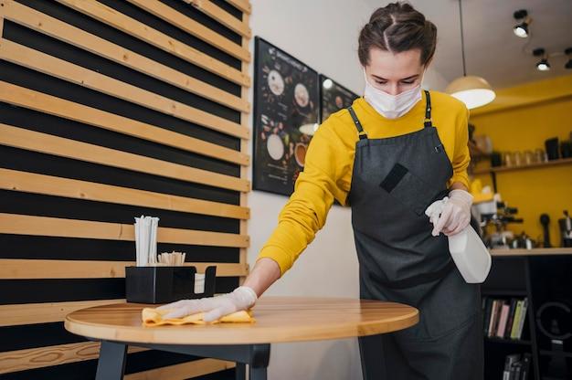 Vrouwelijke barista schoonmaak tafel terwijl het dragen van medische masker Gratis Foto