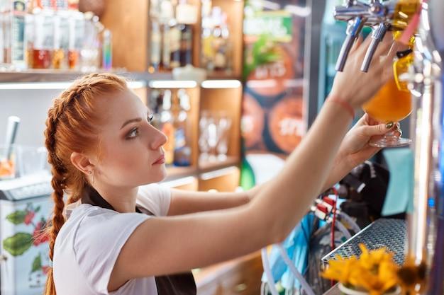 Vrouwelijke barman ambachtelijk bier tappen in staaf Gratis Foto