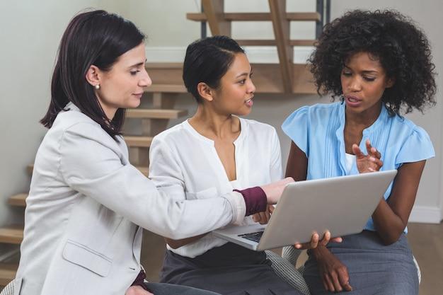 Vrouwelijke bedrijfscollega's die op laptop bespreken Premium Foto