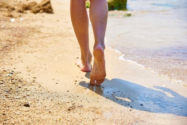 Vrouwelijke benen gaan langs de kust van de zee op een zonnige dag. Premium Foto