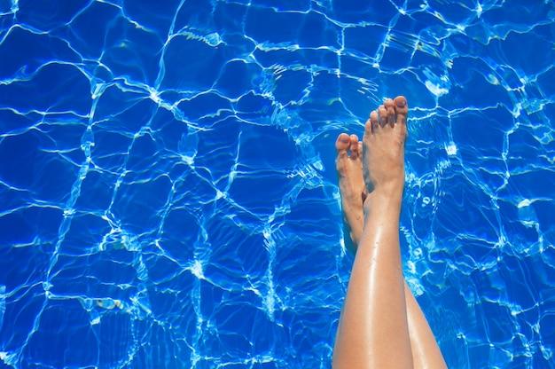 Vrouwelijke benen in blauwe waterpool Premium Foto