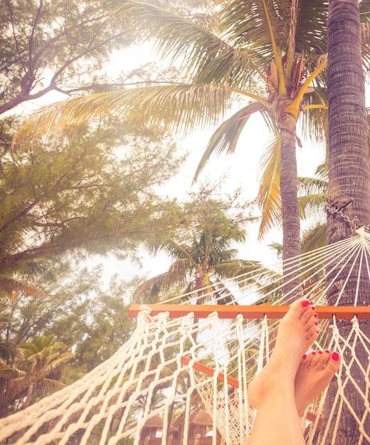 Vrouwelijke benen in een hangmat op een achtergrond van de zee, palmbomen en zonsondergang Premium Foto