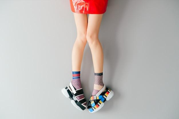 Vrouwelijke benen in modieuze niet-overeenkomende sokken en schoenen over grijs Premium Foto