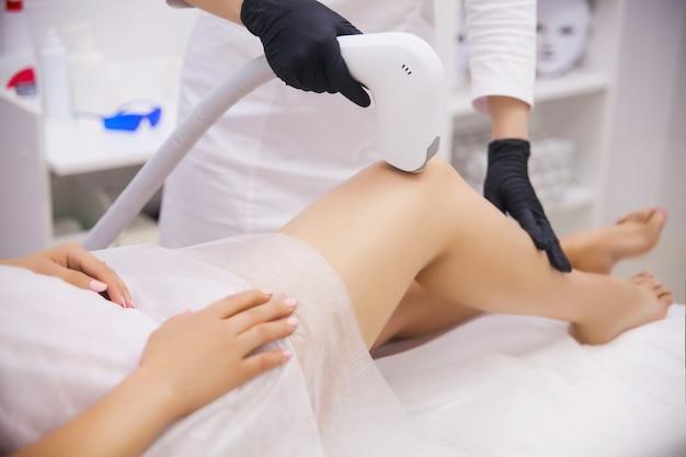 Vrouwelijke benen, vrouw in professionele schoonheidskliniek tijdens laser ontharing Premium Foto