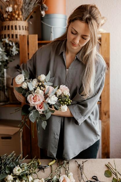 Vrouwelijke bloemist die een mooi bloemenarrangement maakt Gratis Foto