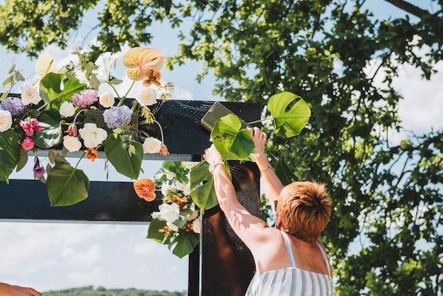 Vrouwelijke bloemist die een ongebruikelijke zwarte huwelijksboog verfraait Premium Foto