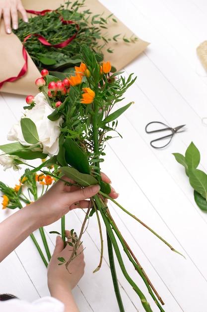Vrouwelijke bloemist die mooi boeket maakt bij bloemenwinkel Gratis Foto