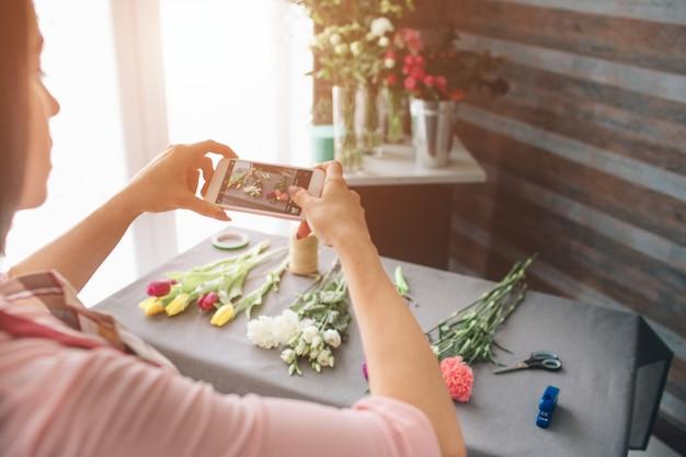 Vrouwelijke bloemist op het werk: mooie jonge donkerharige vrouw mode moderne boeket van verschillende bloemen maken. vrouwen die werken met bloemen in de werkplaats. ze fotografeert bloemen op een smartphone. Premium Foto