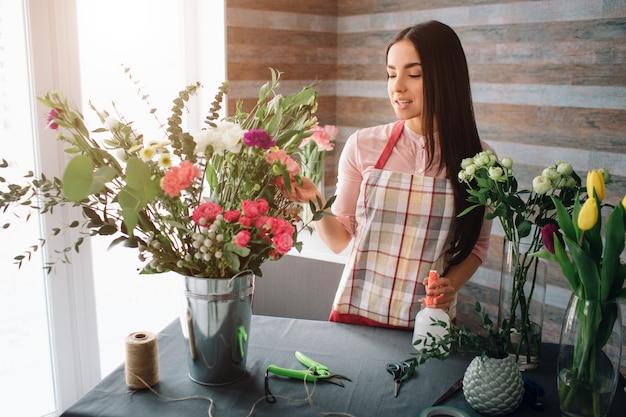 Vrouwelijke bloemist op het werk: vrij jonge donkerharige vrouw mode modern boeket van verschillende bloemen maken. vrouwen die met bloemen in workshop werken Premium Foto