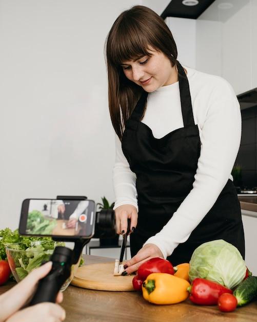 Vrouwelijke blogger die zichzelf opneemt terwijl ze een salade met groenten klaarmaakt Gratis Foto