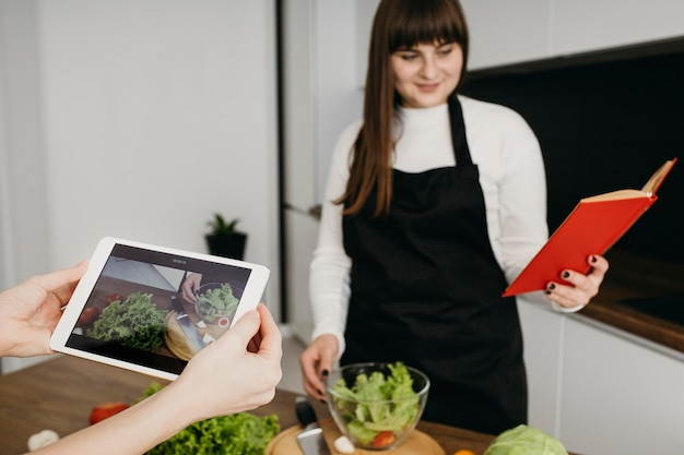 Vrouwelijke blogger die zichzelf opneemt tijdens het bereiden van eten en het lezen van een boek Gratis Foto