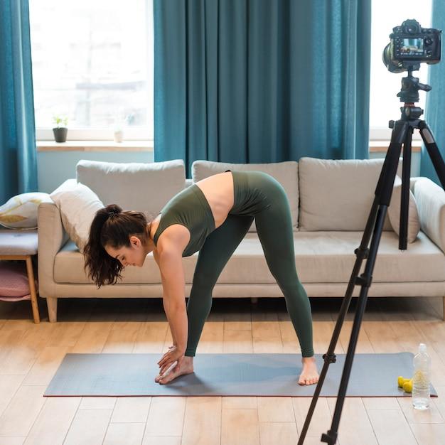 Vrouwelijke blogger in sportkleding en stretching Gratis Foto