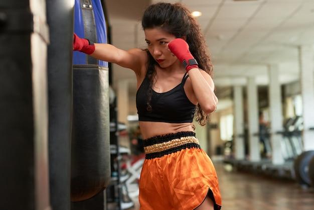 Vrouwelijke bokser het beoefenen van stoten op bokszak in een sportschool Gratis Foto