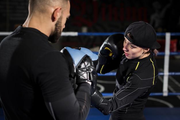 Vrouwelijke bokser in de ring training met beschermende handschoenen Gratis Foto