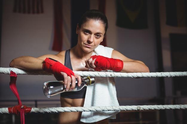 Vrouwelijke bokser met waterfles in boksring Gratis Foto