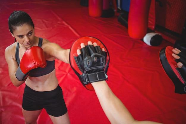 Vrouwelijke bokser oefenen met trainer Gratis Foto