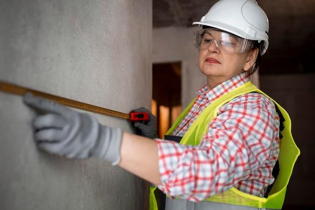 Vrouwelijke bouwvakker met helm en meetlint Gratis Foto