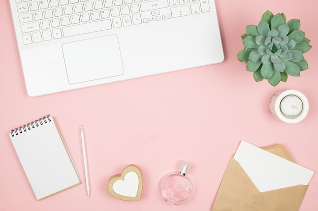 Vrouwelijke bureaudesktop met kantooraccessoires op roze oppervlak. dameswerkruimte met vetplanten, kaarsen en cosmetica. Premium Foto