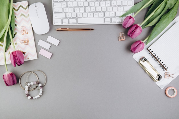 Vrouwelijke bureauwerkruimte met tulpen, toetsenbord, agenda en gouden klemmen op grijs Premium Foto